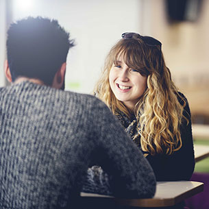 Two people talking at a table in Onezone on Frenchay Campus
