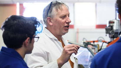 A lecturer in a lab talking to two students