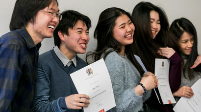 Group of international students holding certificates.