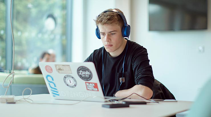 Student working at a laptop in study space