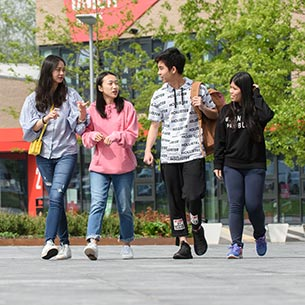 Four international students walking on Frenchay Campus