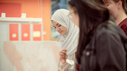 Students looking at designs printed on large-format paper.
