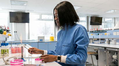Student working in a lab while wearing a blue coat.