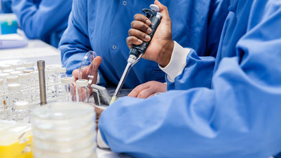 Two people wearing blue gowns conducting research with petri dishes