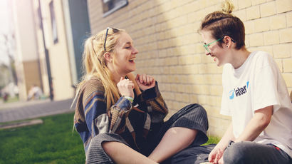 A couple of students laughing outside their accommodation.