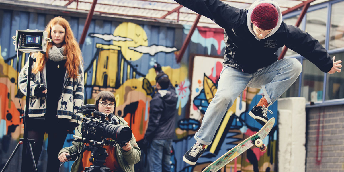 Students filming a skateboarder jumping in front of a graffiti wall